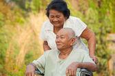 Starší žena tlačí manžela postižené na vozíku — Stock fotografie