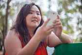 Happy fatty woman using mobile phone — Stock Photo