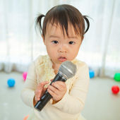 Little asian girl with microphone — Stock Photo