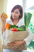 Young Woman with vegetables in shopping bag — Stock Photo
