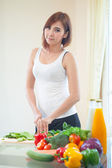 Happy woman cooking vegetables green salad — ストック写真