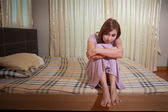 Sad woman sitting on the bed — Stock Photo