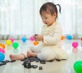 Little girl playing with black domino — Stock Photo