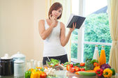 Young woman reads cookbook — Stock Photo