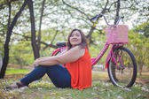 Happy fatty woman posing with bicycle — Stock Photo