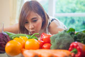 Happy woman cooking vegetables green salad — Stock Photo