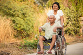 Senior woman pushing her disabled husband on wheelchair — Stock Photo