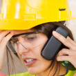Stock Photo: Portrait of a woman with safety helmet and mobile phone