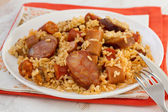 Rice with sausages on the white plate — Stock Photo