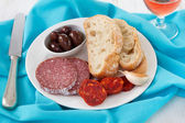 Sausages with olives and bread on the plate — Stock Photo