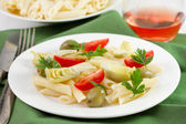 Artichoke salad with penne and tomato on the white plate — Stock Photo