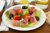 Salad with prosciutto, olives, lettuce on the plate — Stock Photo