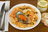 Seafood rice on the plate with glass of water — Stock Photo