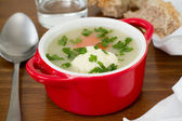 Cauliflower soup in red bowl with spoon — Stock Photo