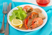 Fish with srimps and claims on the plate — Stock Photo