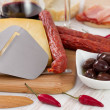 Cheese with sausages, olives and red wine — Stock Photo