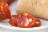 Smoked sausage with bread on the plate — Stock Photo