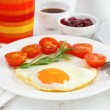 Fried egg with tomato cherry on the white plate — Stock Photo #19095557