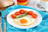 Fried egg with tomato cherry on the white plate — Stock Photo