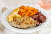 Fried pork with chourico, pumpkin and apple on the plate — Stock Photo