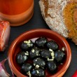 Black olives with garlic in ceramic dish - Stock Photo