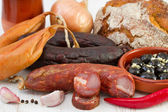 Smoked sausages with onion, olives and bread — Stock Photo