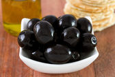 Black olives with oil and toasts — Stock Photo