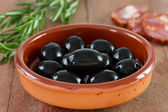 Black olives in dish with sausages — Stock Photo