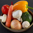 Vegetables in the old dish on dark background — Stock Photo