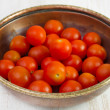 Small tomato in old dish - Stock Photo