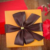 Orange gift box with flower — Stock Photo