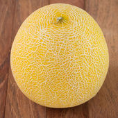 Yellow melon on brown table — Stock Photo