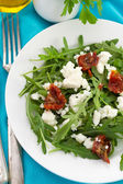 Rucola with cottage cheese and dry tomato — Stock Photo