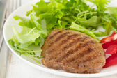 Grilled meat with lettuce on white plate — Stock Photo