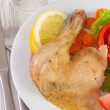Stock Photo: Chicken with salad and lemon on white plate