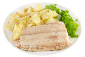 Boiled fish with potato and lettuce on white plate — Stock Photo