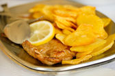 Fried meat with potato and lemon — Stock Photo
