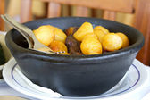 Potato with meat in black dish — Stock Photo