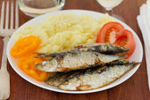 Fried sardines with potato on the plate — Stock Photo