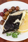 Fish with olives and lemon on white plate — Stock Photo