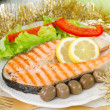 Salmon with lemon, salad and olives — Stock Photo
