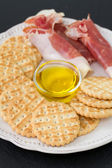 Prosciutto with cookies and oil — Stockfoto