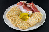 Prosciutto with cookies and oil — Stock Photo