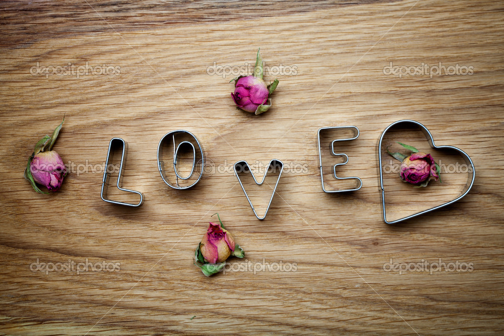 Letters of love cookie cutters with dried roses — Stock Photo #12110758