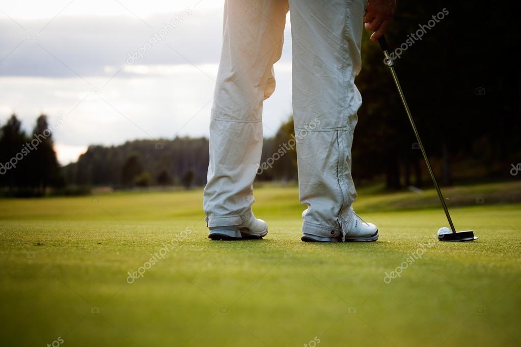 Male golfer putting a golf ball in to hole  Stock Photo #12316582