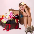 Young pin up woman sitting near her suitcase — Stock Photo