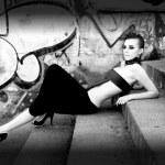 Beautiful futuristic woman near graffiti wall, monochrome — Stock Photo