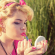 Blond pinup girl checking makeup — Stock Photo