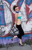 Futuristic woman with creative hairstyle near graffiti wall — Foto de Stock