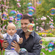 Father and his child playing with soap bubbles — Stock Photo